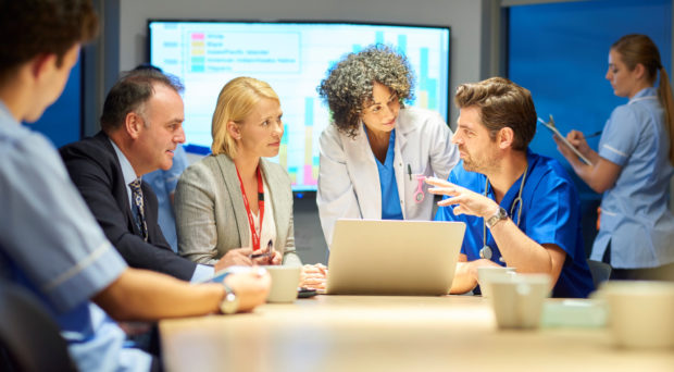 a mixed group of healthcare professional and business people meet around a conference table