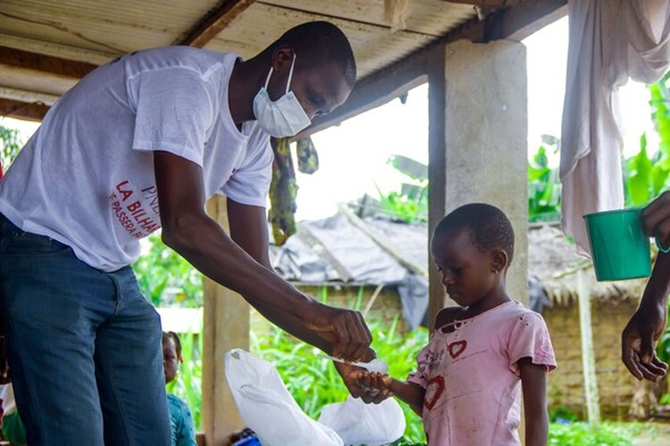 A man with a mask covering his moth and nose, is placing a medicine tablet into the hands of a young girl woth a pink shirt on.
