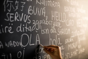 """Hello"" written in several languages on a blackboard"