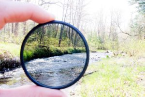 A neutral density filter held in front of a landscape