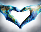 hands shaped heart with world map