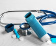 Asthma inhaler, stethoscope and pills on white wooden background