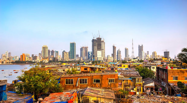 Mumbai cityscape with informal settlements in the foreground and skyscrapers behind