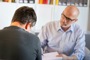 Mature male psychotherapist or counsellor interacts with a male client during a one-to-one therapy session.