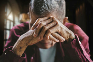 An older person covering their face with their hands